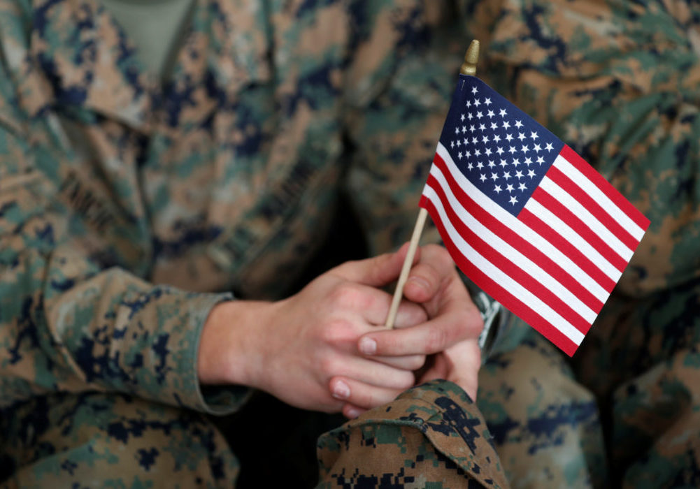 A soldier holds a flag as U.S. President Donald Trump speaks at Marine Corps Air Station Miramar in San Diego, California, U.S. March 13, 2018. REUTERS/Kevin Lamarque - RC1E9090D5E0
